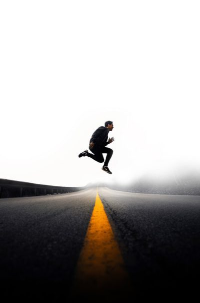 Man jumping across the road high energy