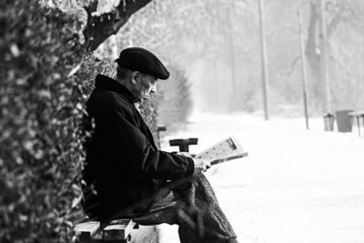 Man on a park bench reading a paper